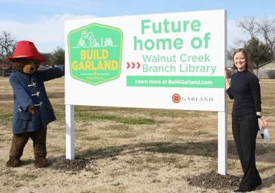 Picture of Paddington Bear and the library director standing alongside the new library sign